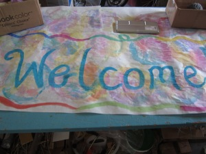 "A water colored ""welcome"" sign for the entry bulletin board"