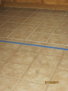 the grout lines above the blue painter's tape have been treated, the lines below are the original grout lines